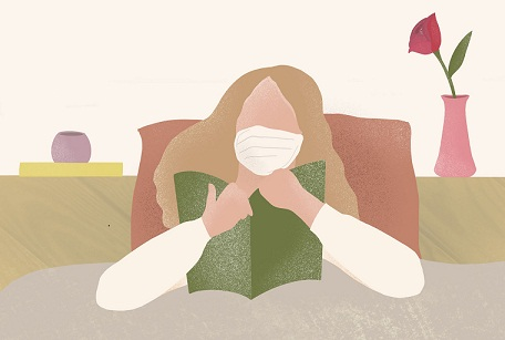 A sick woman wearing a medical face mask and reading a book.  (iStock)